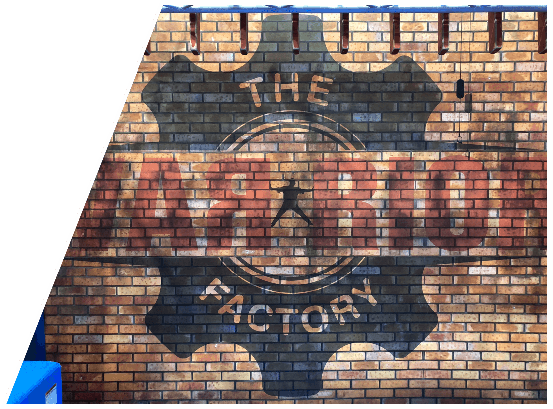 A brick wall with The Warrior Factory logo on it